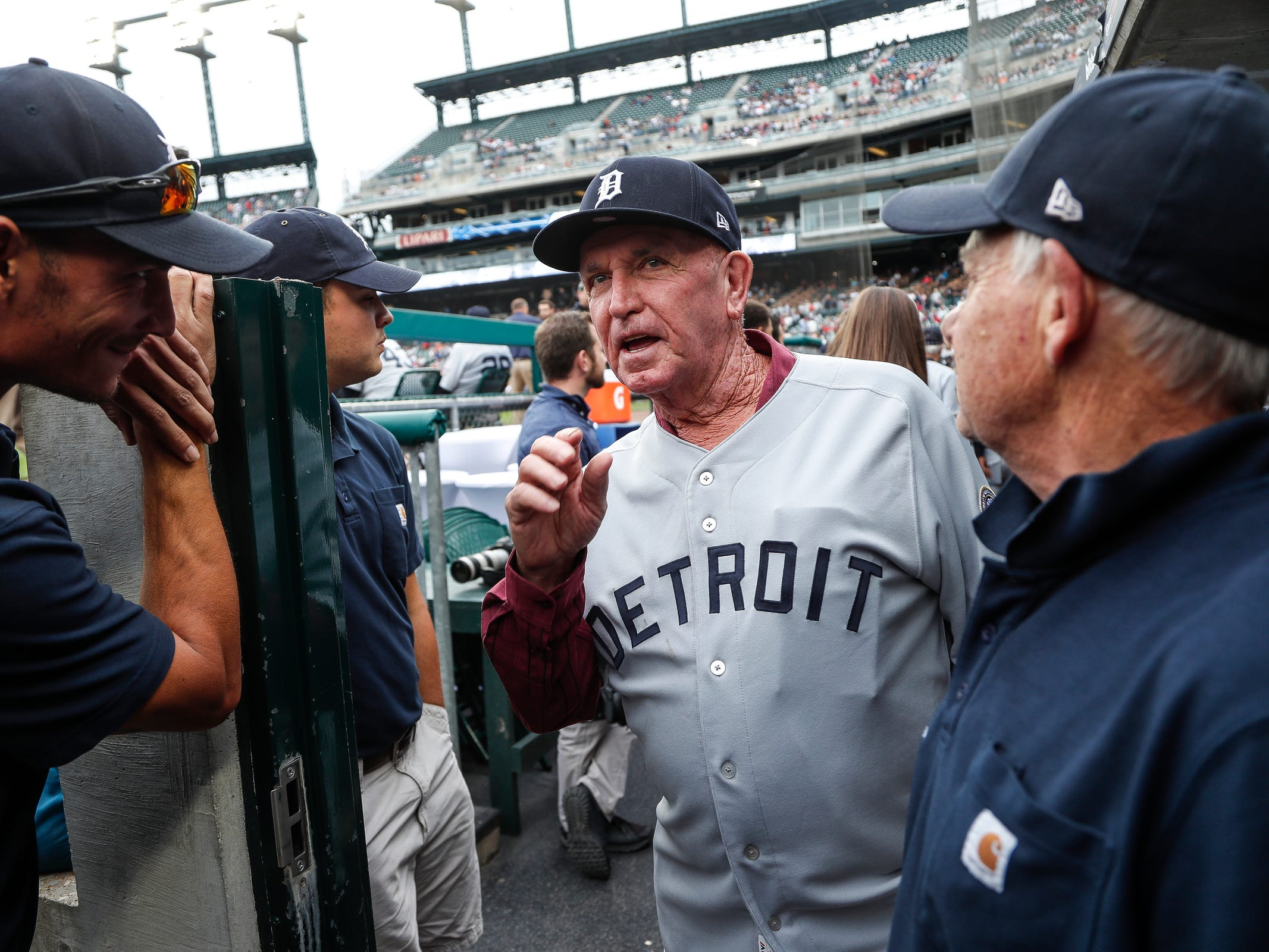 Former Detroit Tigers outfielder Wayne Comer, center, talks to ground crew Andrew Goodrich, left, Adam Thompson, center, and Dennis Wilson in the dugout during the celebration of the 50th anniversary of 1968 World Series championship at Comerica Park in Detroit, Saturday, Sept. 8, 2018.