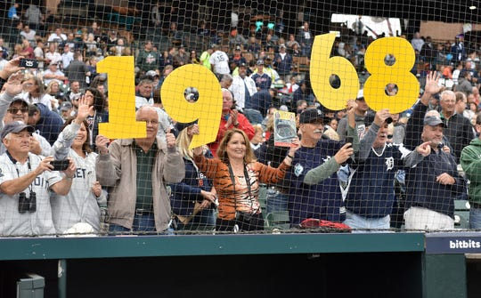 Fans hold up the numbers 1968 at the end of the pregame ceremony honoring the World Series championship team.
