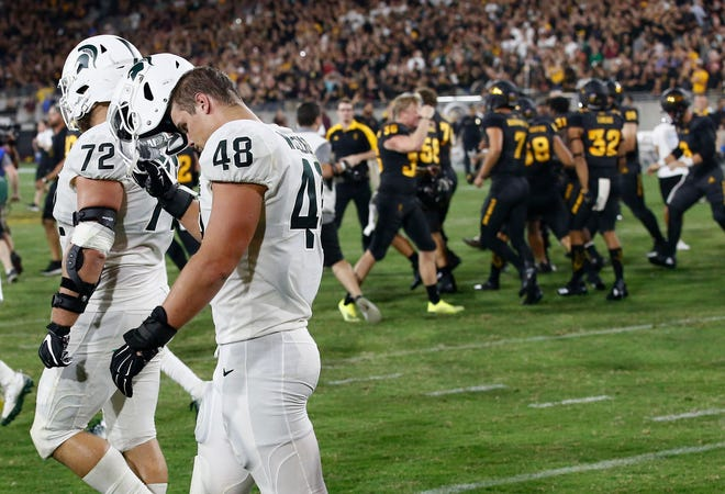 As Arizona State players celebrate a winning field goal, Michigan State defensive end Kenny Willekes (48) and defensive tackle Mike Panasiuk walk off the field Saturday night.