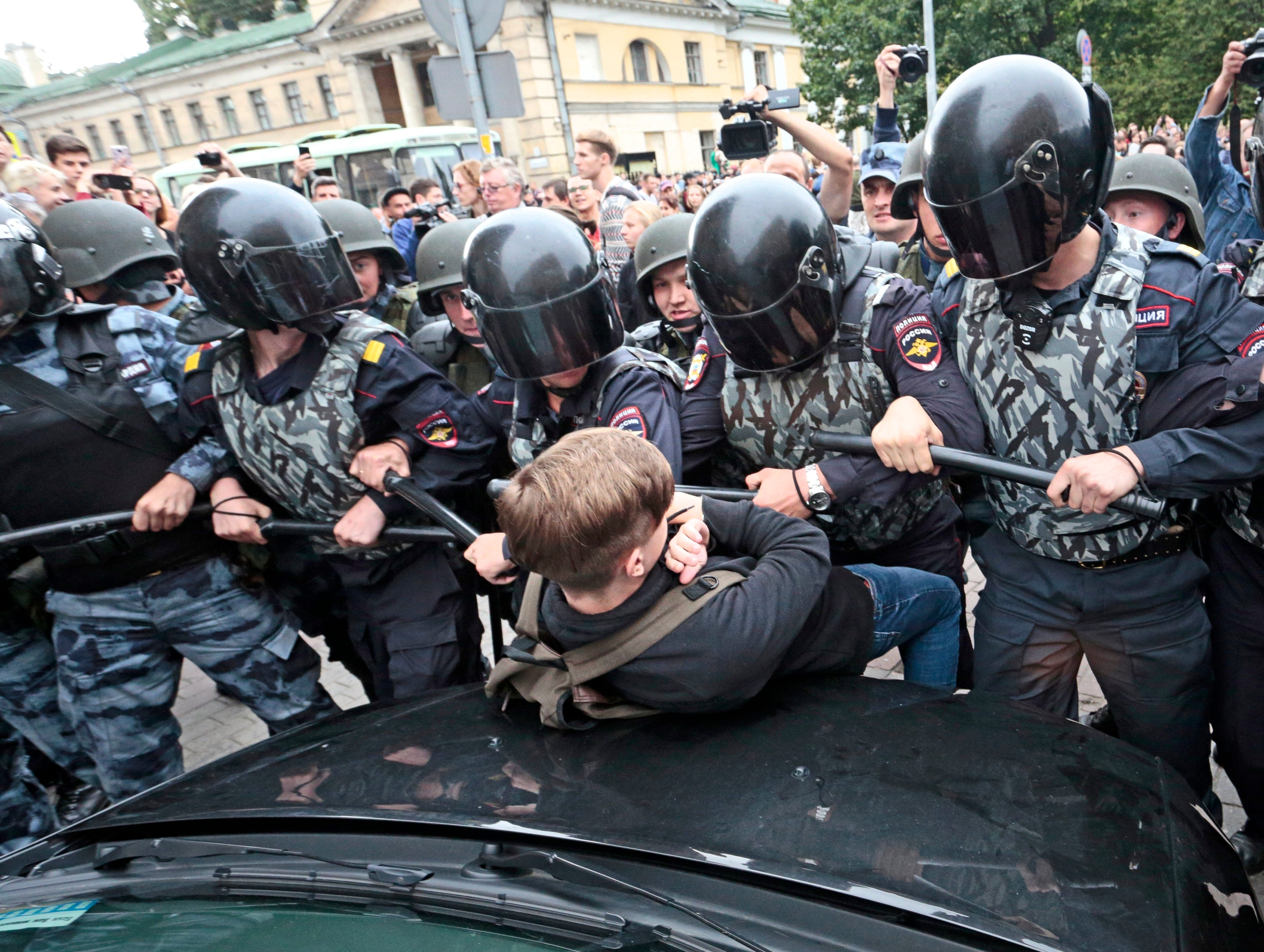 Russian police officers push a teenager during a rally protesting retirement age hikes in St. Petersburg, Russia, Sunday, Sept. 9, 2018. A government plan to increase the age for collecting state pensions brought protests across Russia's 11 time zones on Sunday even though the opposition leader who called them was in jail. Nearly 300 people were reported arrested.
