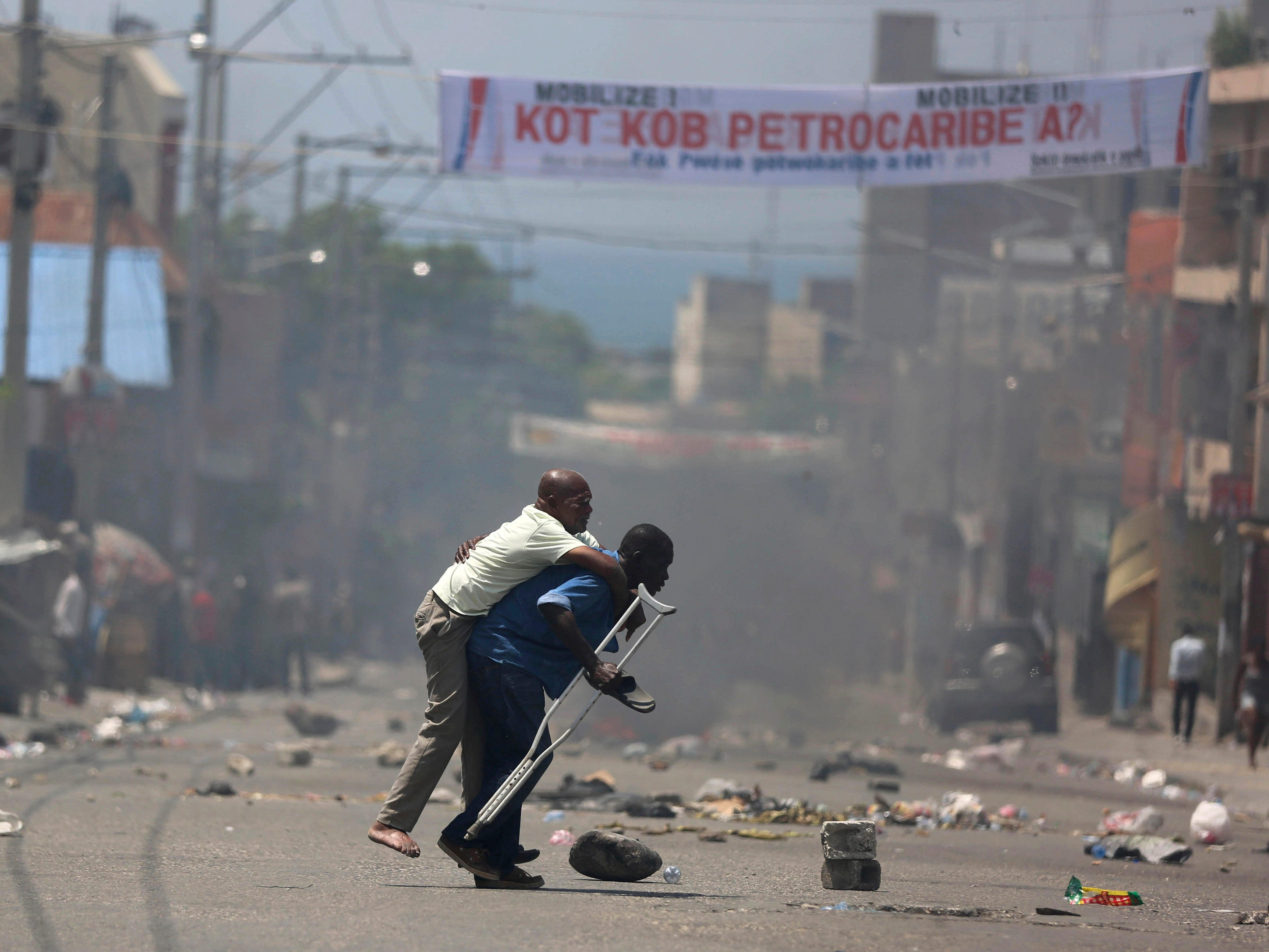 A handicapped man is carried across the street as police firie tear gas at protesters demanding to know how PetroCaribe funds have been used by the government, in Port-au-Prince, Haiti, Sunday, Sept. 9, 2018. Much of the financial support to help Haiti rebuild after the 2010 earthquake comes from Venezuela's PetroCaribe fund, a 2005 pact that gives suppliers below-market financing for oil and is under the control of the central government. Protesters say many projects are unfinished and that officials have inflated costs in order to steal money.