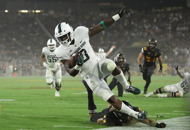 Michigan State running back LJ Scott is tackled after a reception against Arizona State.