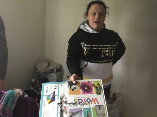 Danielle Stephens shows children's books that were hit by gunfire.