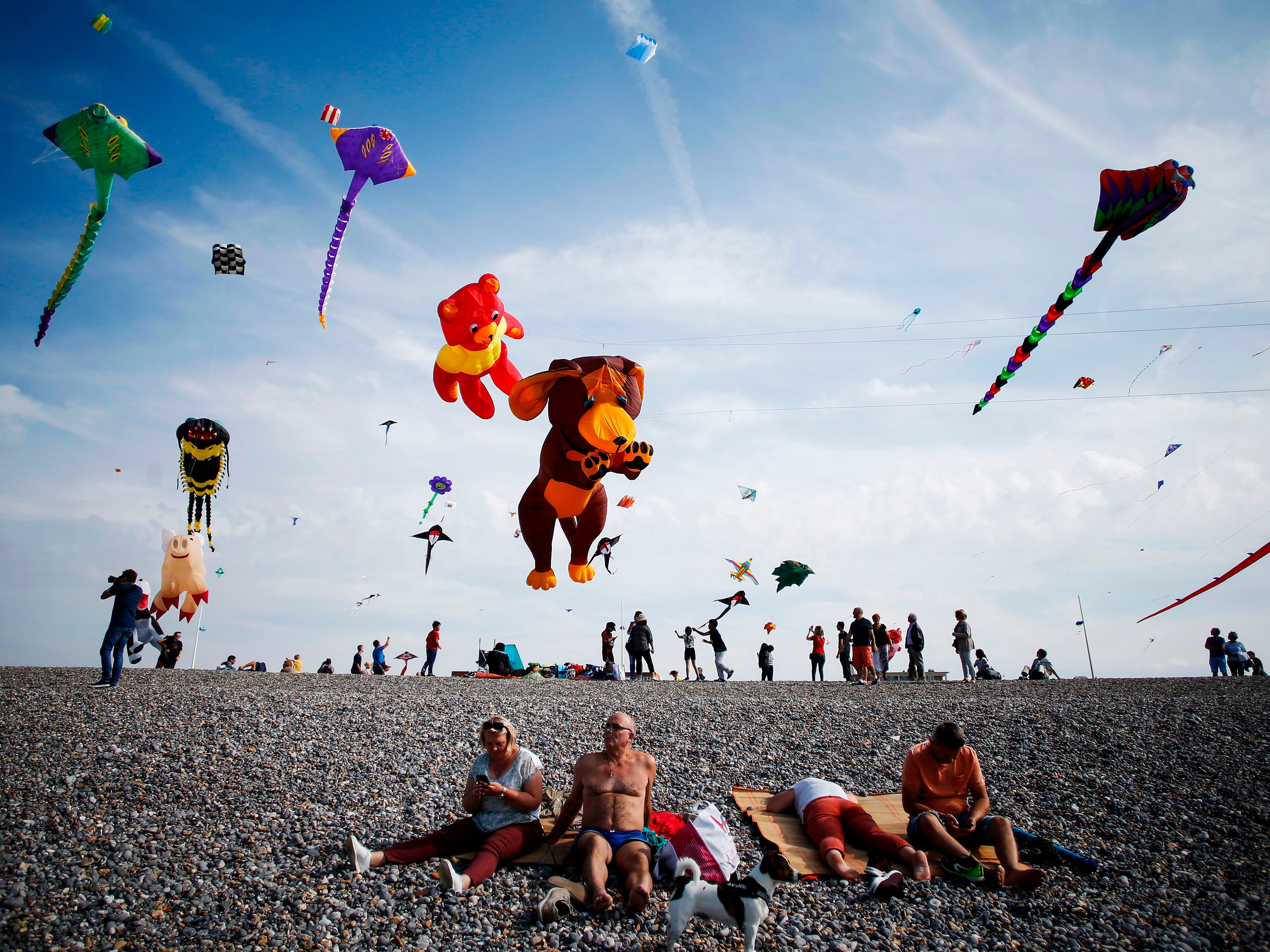People fly kites on a beach while others sunbathe during the 20th edition of the International Dieppe Kite Festival on September 9, 2018, in Dieppe, northwestern France.