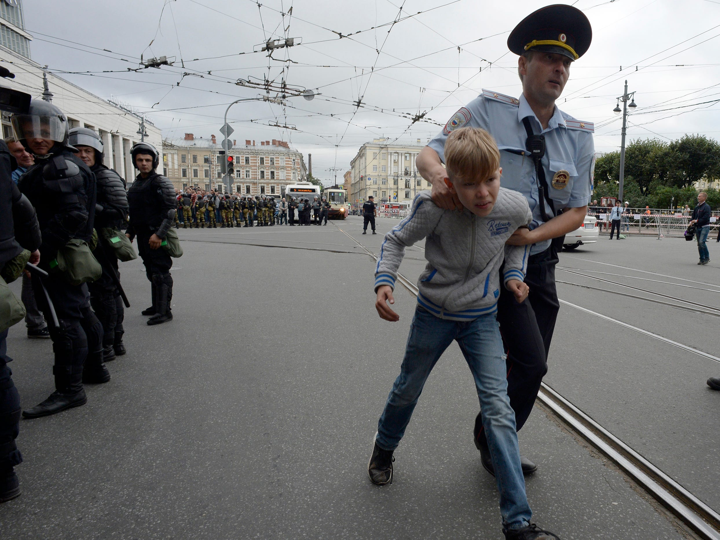 Russian police escort a youth away during a protest rally against planned increases to the nationwide pension age in Saint Petersburg on September 9, 2018.