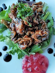 Lure's Ciccia Calimari combines lightly crisp fried calimari strips with a tangy balsamic sauce, fresh greens, and pickled onion jam.