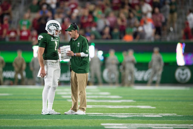 CSU football coach Mike Bobo talks with quarterback K .J. Carta-Samuels during a Sept. 8 win over Arkansas at Canvas Stadium. Bobo said Wednesday that he'll continue to play two quarterbacks -- Carta Samuels and Collin Hill -- in the Rams' game Saturday night at San Jose State.