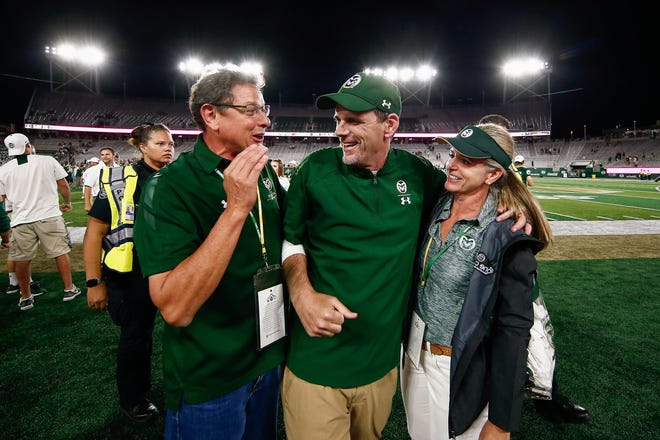 Brett Anderson (L) and Dawn Anderson (R) greet Colorado State Rams head coach Mike Bobo (C) after the game against the Arkansas Razorbacks at Canvas Stadium.
