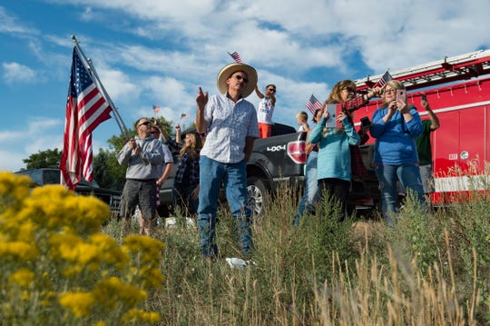 People wave for veterans participating in Honor Flight Northern Colorado as they drive by on I-25 on their way to Denver International Airport in Loveland on Sunday, September 9, 2018. Honor Flight Northern Colorado sent one last group of veterans to Washington D.C. to visit war memorials in the nation's capital.