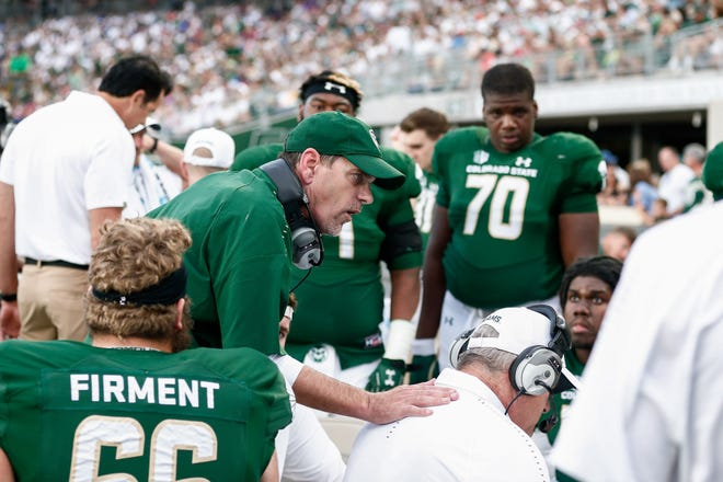 CSU coach Mike Bobo talks to offensive players on the sideline during the second quarter of Saturday night's home game against Arkansas. Quarterbacks coach Ronnie Letson was calling the Rams' offensive plays from the coaches' booth in the press box, Bobo said, although the head coach intervened for two critical calls late in the game as CSU rallied from 18 points down for a 34-27 win.