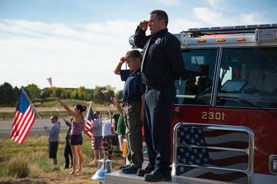 Eaton firefighter Chris Vilkaitis salutes with his son, Jack, 10, as veterans participating in Honor Flight Northern Colorado drive by on I-25 in Loveland on Sunday, September 9, 2018. Honor Flight Northern Colorado sent one last group of veterans to Washington D.C. to visit war memorials in the nation's capital.