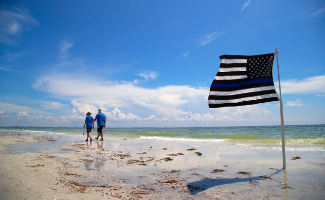 Area beachgoers are starting to return to the beaches of Sanibel and Captiva as the red tide outbreak lessens. Pat and David Leonardi, not pictured, chose to honor law enforcement officers Sunday by flying a blue line American flag as they enjoyed the beach.