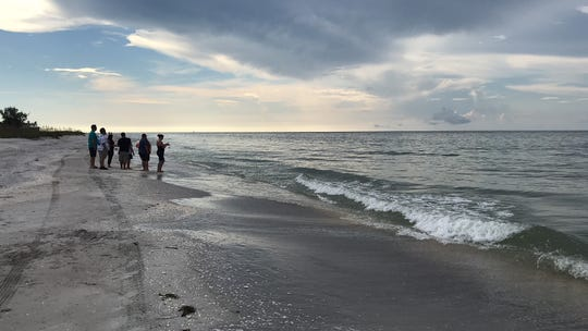 A group of Orlando residents on a eco-tour walk the beach near the Island Inn on Sanibel early on Sunday. The group was surprised at the lack of effects from red tide.