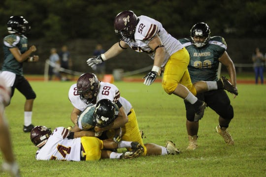 FD Friars, including defensive standout Rylan Napoleon, in the air, swarm the runner during a IIAAG High School Football game against the JFK Islanders at John F. Kennedy field.