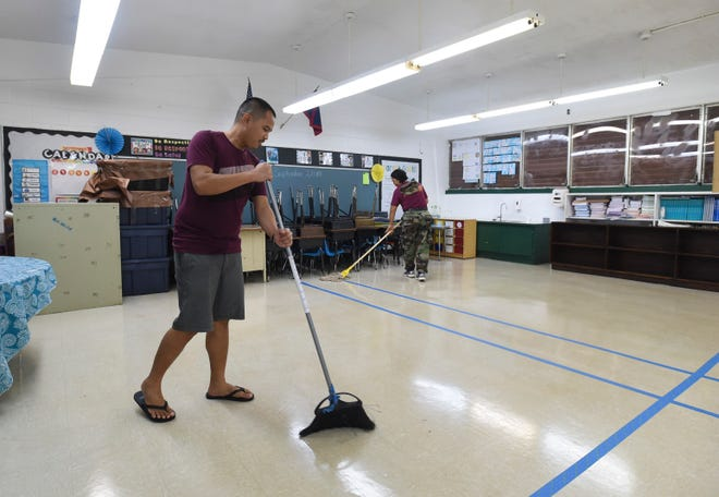 Maria A. Ulloa Elementary School employees Erwin Aguon and Belmarie Toves sweep a classroom while preparing it for storm shelter on Sept. 9, 2018.