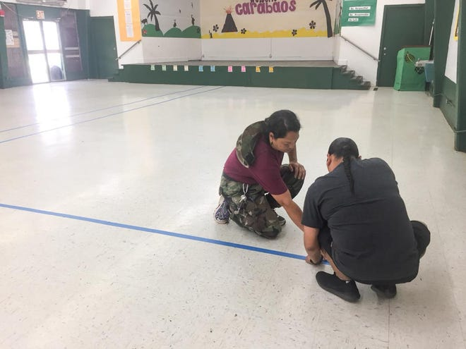 Maria A. Ulloa Elementary School employees prepare shelter spaces in their school cafeteria.