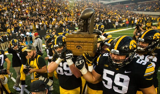 Iowa offensive lineman Keegan Render (69) and Iowa offensive lineman Ross Reynolds (59) carry the Cy-Hawk trophy after the Cy-Hawk NCAA football game on Saturday, Sept. 8, 2018, at Kinnick Stadium in Iowa City. The Hawkeyes defeated the Cyclones, 13-3.
