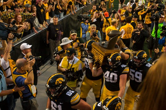 Iowa offensive lineman Keegan Render (69) defensive end Parker Hesse (40) and offensive lineman Ross Reynolds (59) carry the Cy-Hawk trophy after the Cy-Hawk NCAA football game on Saturday, Sept. 8, 2018, at Kinnick Stadium in Iowa City. The Hawkeyes defeated the Cyclones, 13-3.