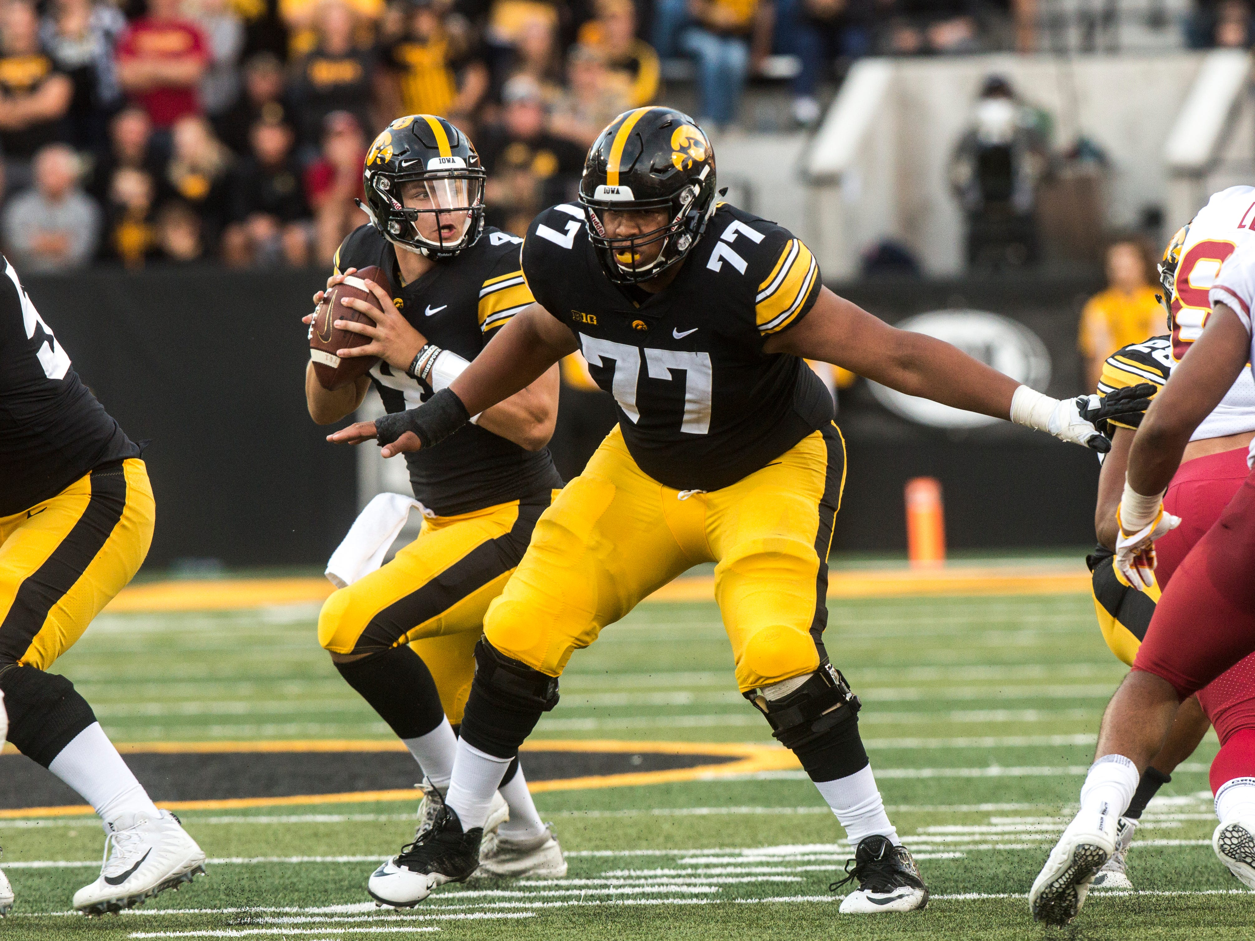 Iowa quarterback Nate Stanley (4) looks to pass while offensive lineman Alaric Jackson (77) protects the pocket during the Cy-Hawk NCAA football game on Saturday, Sept. 8, 2018, at Kinnick Stadium in Iowa City.