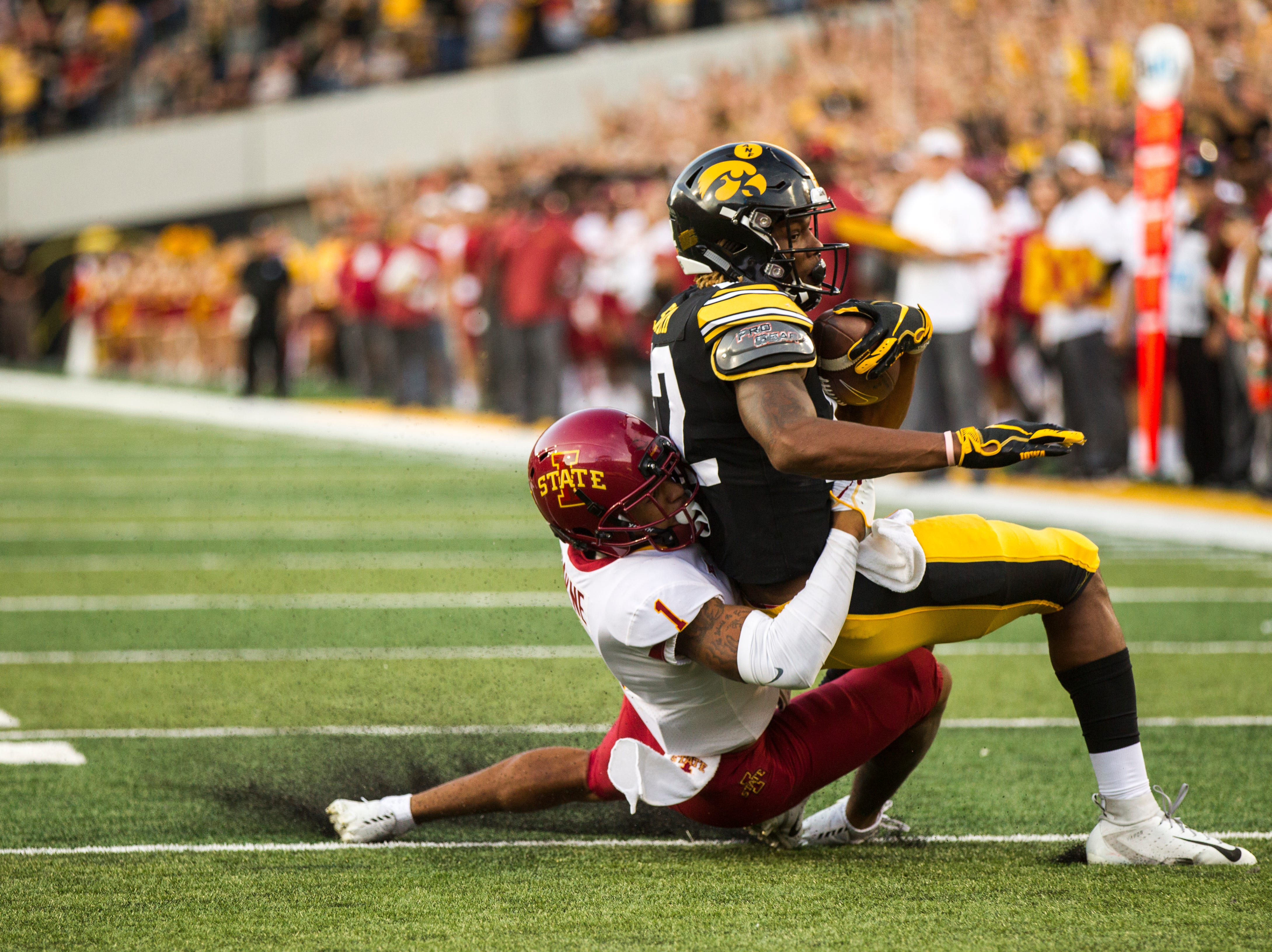 Iowa wide receiver Brandon Smith (12) gets tackled by Iowa State defensive back D'Andre Payne (1) during the Cy-Hawk NCAA football game on Saturday, Sept. 8, 2018, at Kinnick Stadium in Iowa City.