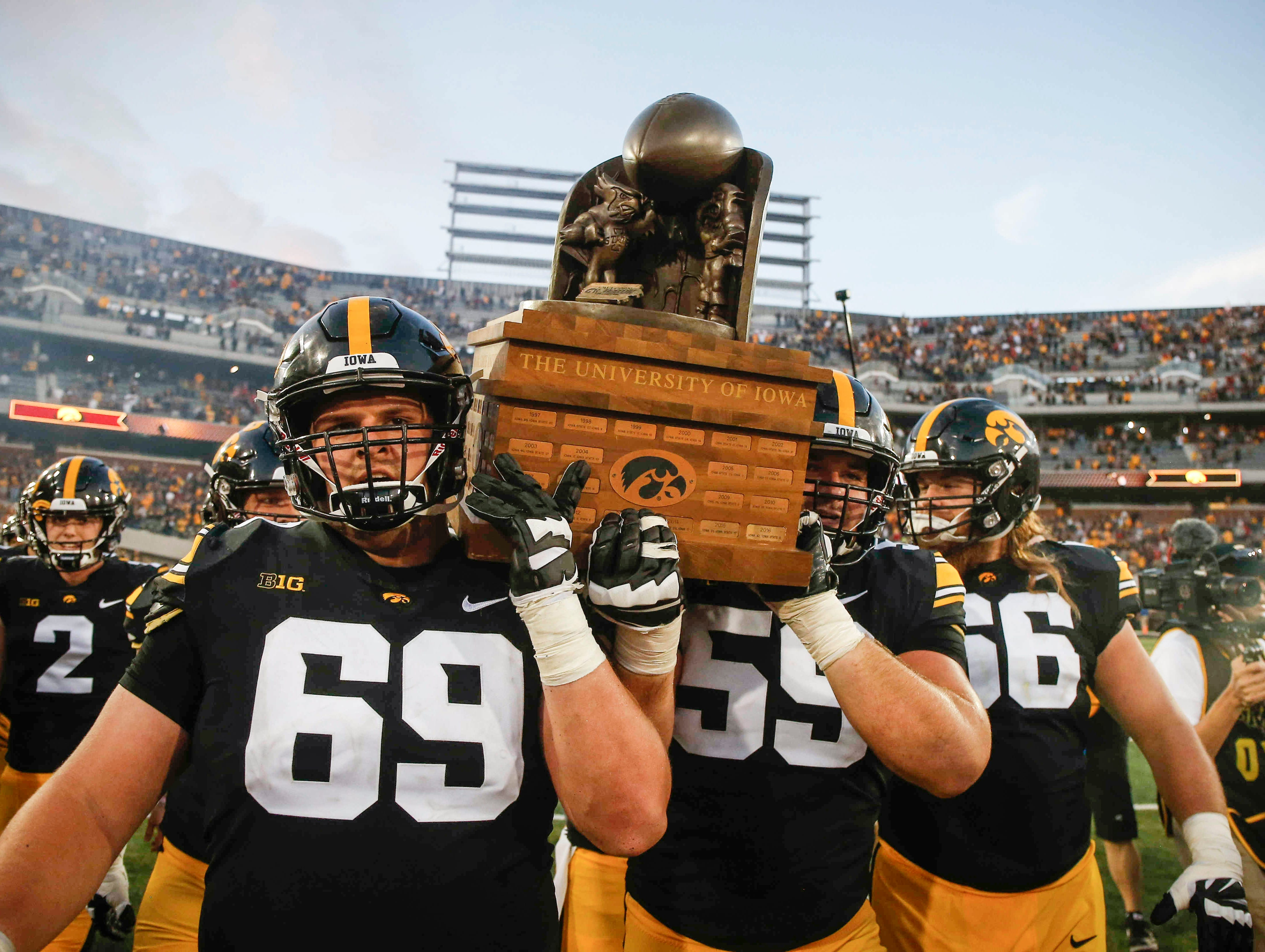 Members of the Iowa Hawkeyes football team carry the CyHawk trophy off the field after a 13-3 win over Iowa State on Saturday, Sept. 8, 2018, at Kinnick Stadium in Iowa City.