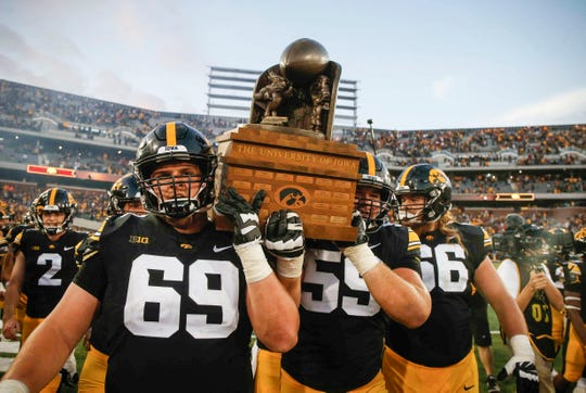 Senior center Keegan Render, of Indianola, leads the march to the Iowa locker room with the Cy-Hawk trophy on Saturday.