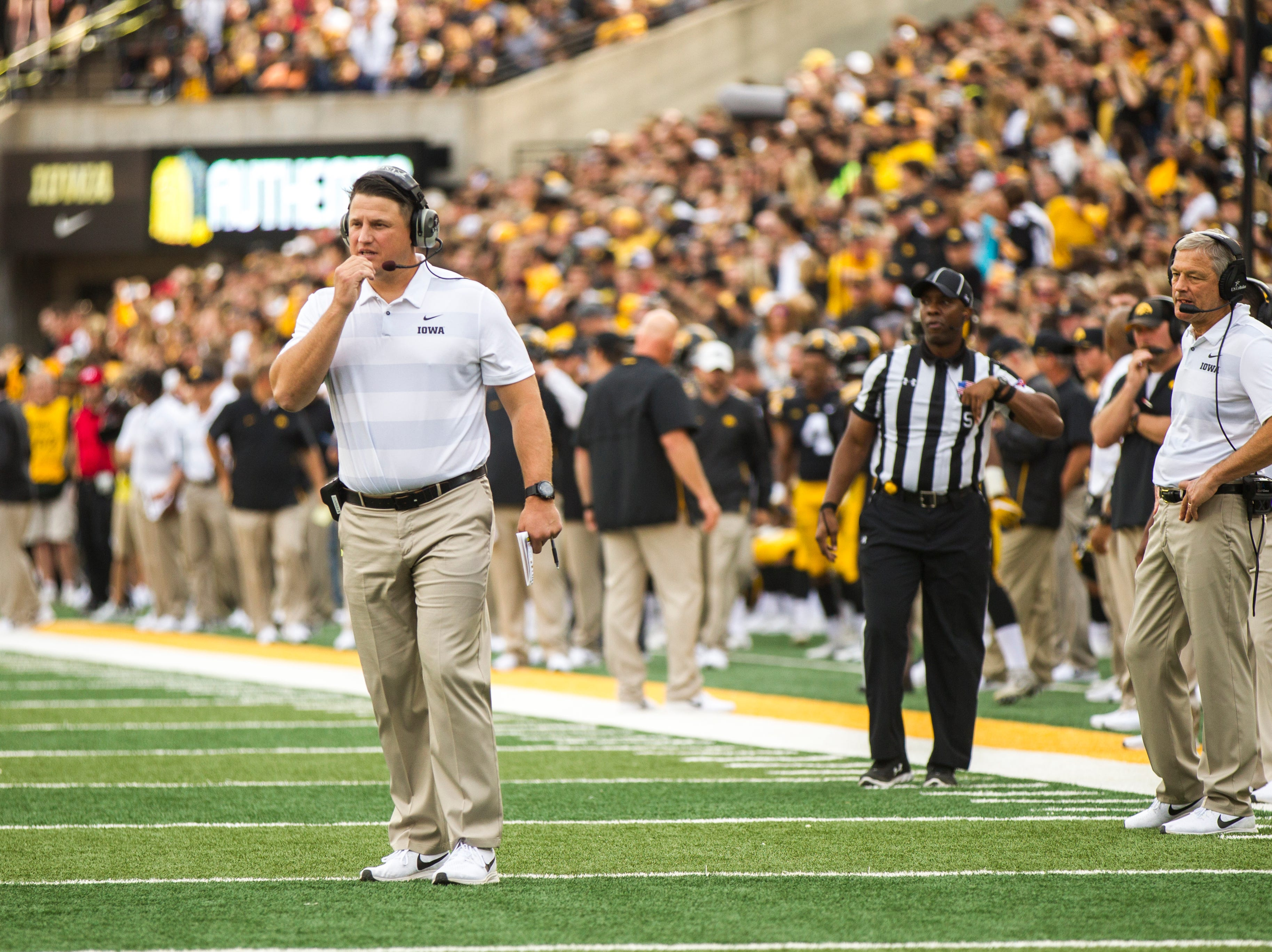 Iowa offensive coordinator Brian Ferentz (left) talks into his headset while Iowa head coach Kirk Ferentz (right) stands on the sideline during the Cy-Hawk NCAA football game on Saturday, Sept. 8, 2018, at Kinnick Stadium in Iowa City.