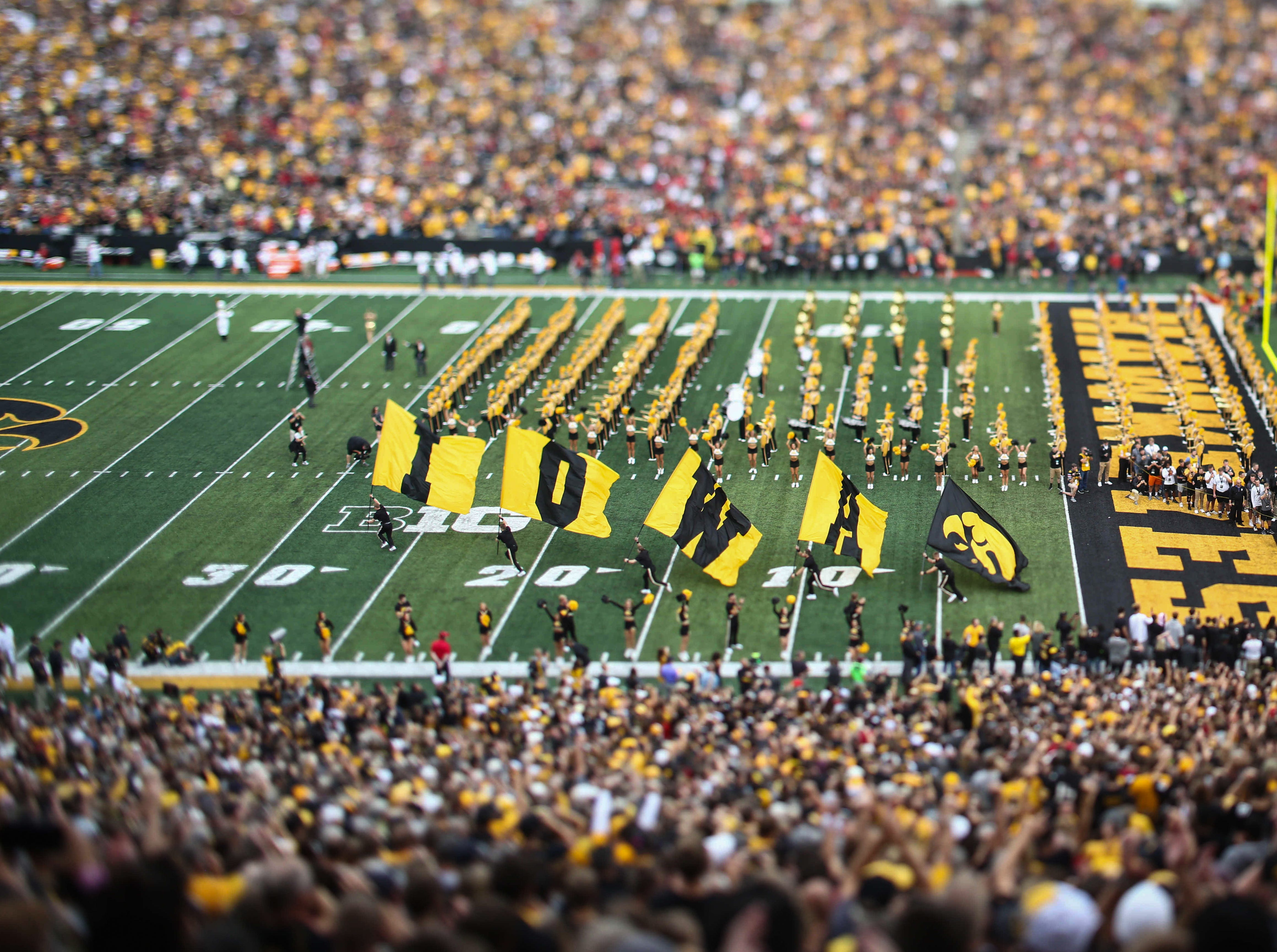 Members of the Iowa Spirit Squad run the Iowa flags onto the field prior to kickoff against Iowa State on Saturday, Sept. 8, 2018, at Kinnick Stadium in Iowa City.