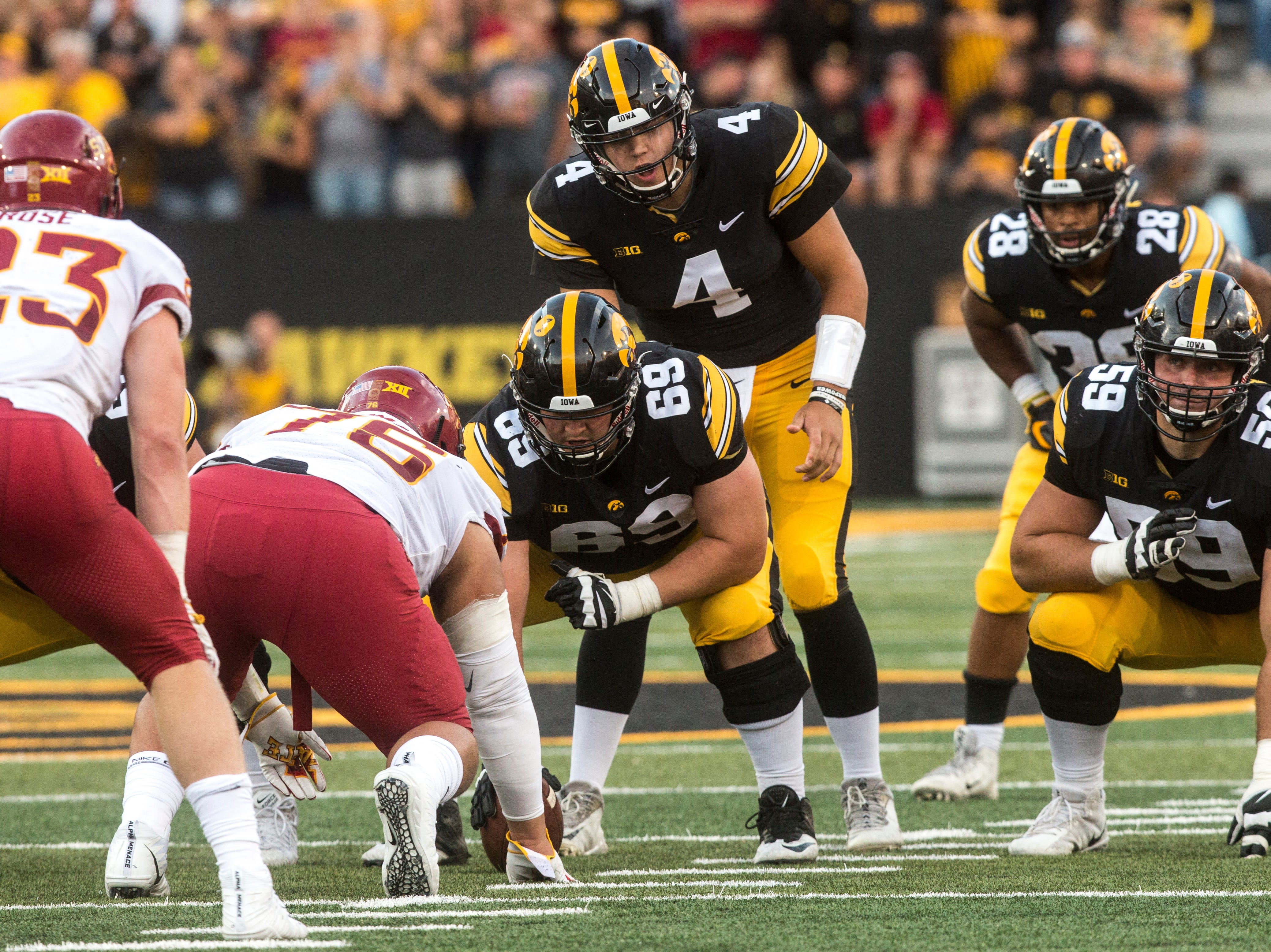Iowa quarterback Nate Stanley (4) takes a snap from offensive lineman Keegan Render (69) while offensive lineman Ross Reynolds (59) gets set during the Cy-Hawk NCAA football game on Saturday, Sept. 8, 2018, at Kinnick Stadium in Iowa City.