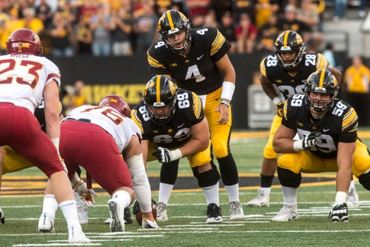 Iowa quarterback Nate Stanley takes a snap from Keegan Render (69) while offensive lineman Ross Reynolds (59) gets set during the Cy-Hawk game on Saturday.
