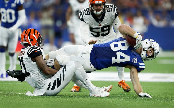 Indianapolis Colts tight end Jack Doyle (84) stretches for more yards as Cincinnati Bengals defensive back Darqueze Dennard (21) attempts to pull him back in the second half of their game at Lucas Oil Stadium on Sept. 9, 2018. The Indianapolis Colts lost to the Cincinnati Bengals 34-23.