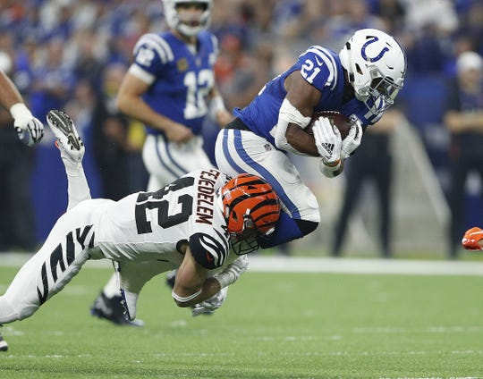Indianapolis Colts running back Nyheim Hines (21) is tackled by Cincinnati Bengals safety Clayton Fejedelem (42) in the first half of their game against the Cincinnati Bengals at Lucas Oil Stadium on Sept. 9, 2018.