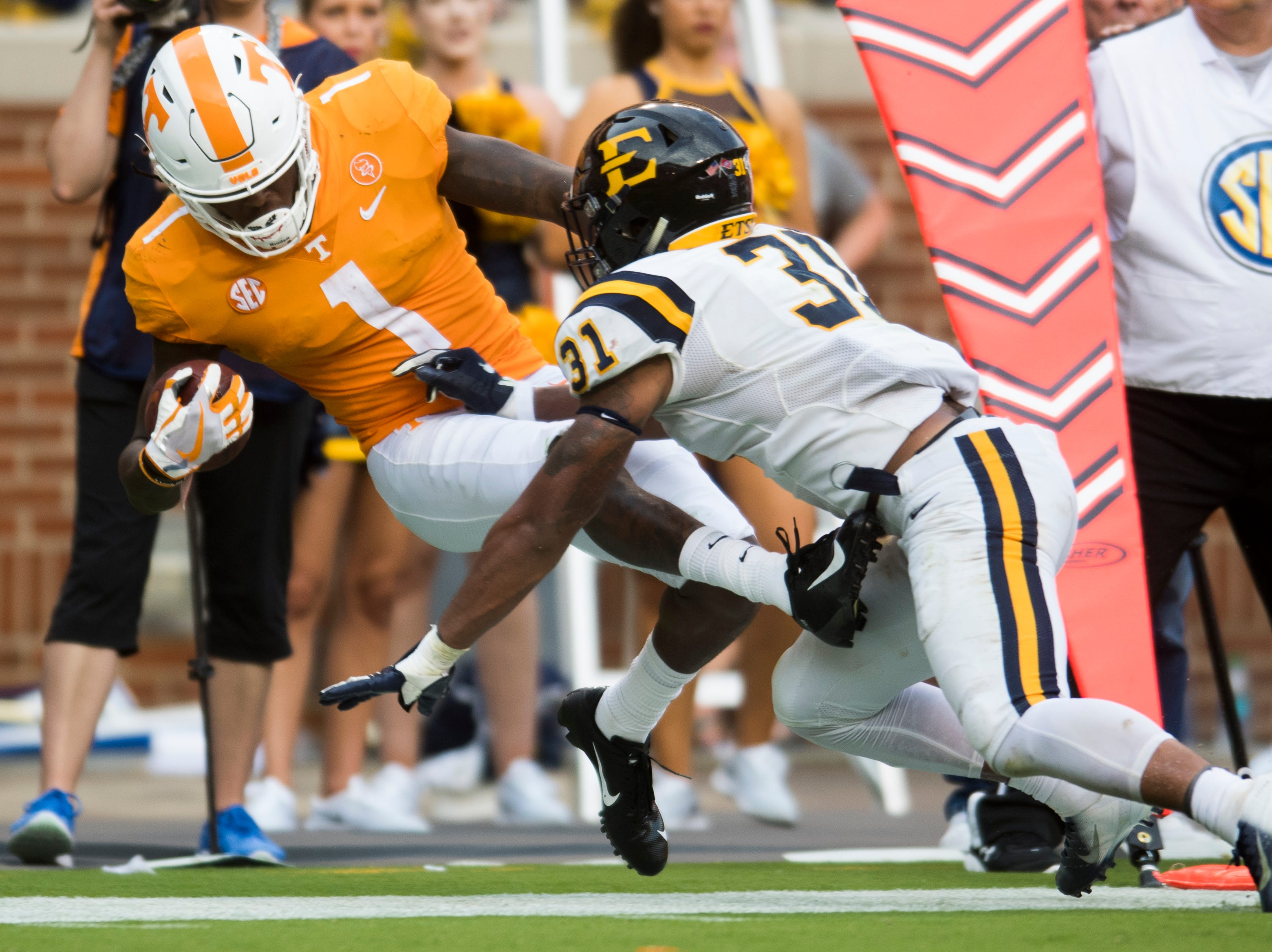 Tennessee wide receiver Marquez Callaway (1) is knocked out of bounds by ETSU linebacker Jared Folks (31) during a game between Tennessee and ETSU at Neyland Stadium in Knoxville, Tennessee on Saturday, September 8, 2018.