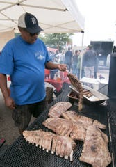 Thomas Mitchell flips ribs on a grill at Big Moe's BBQ & Catering at last year's Brighton's Smokin' Jazz and Barbecue Blues Festival, Saturday, Sept. 8, 2018. The Kalamazoo eatery and catering company will compete again in summer's festival, which runs Friday and Saturday.