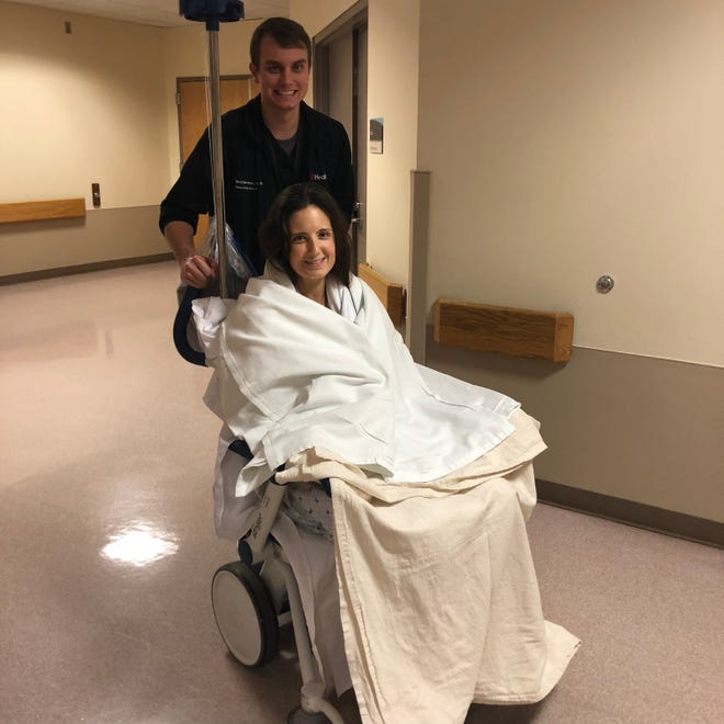 Whitney Austin, 37, the Louisville woman who survived being shot 12 times in Cincinnati, after leaving the surgical intensive care unit. Pictured with nurse Robbie Thomas.