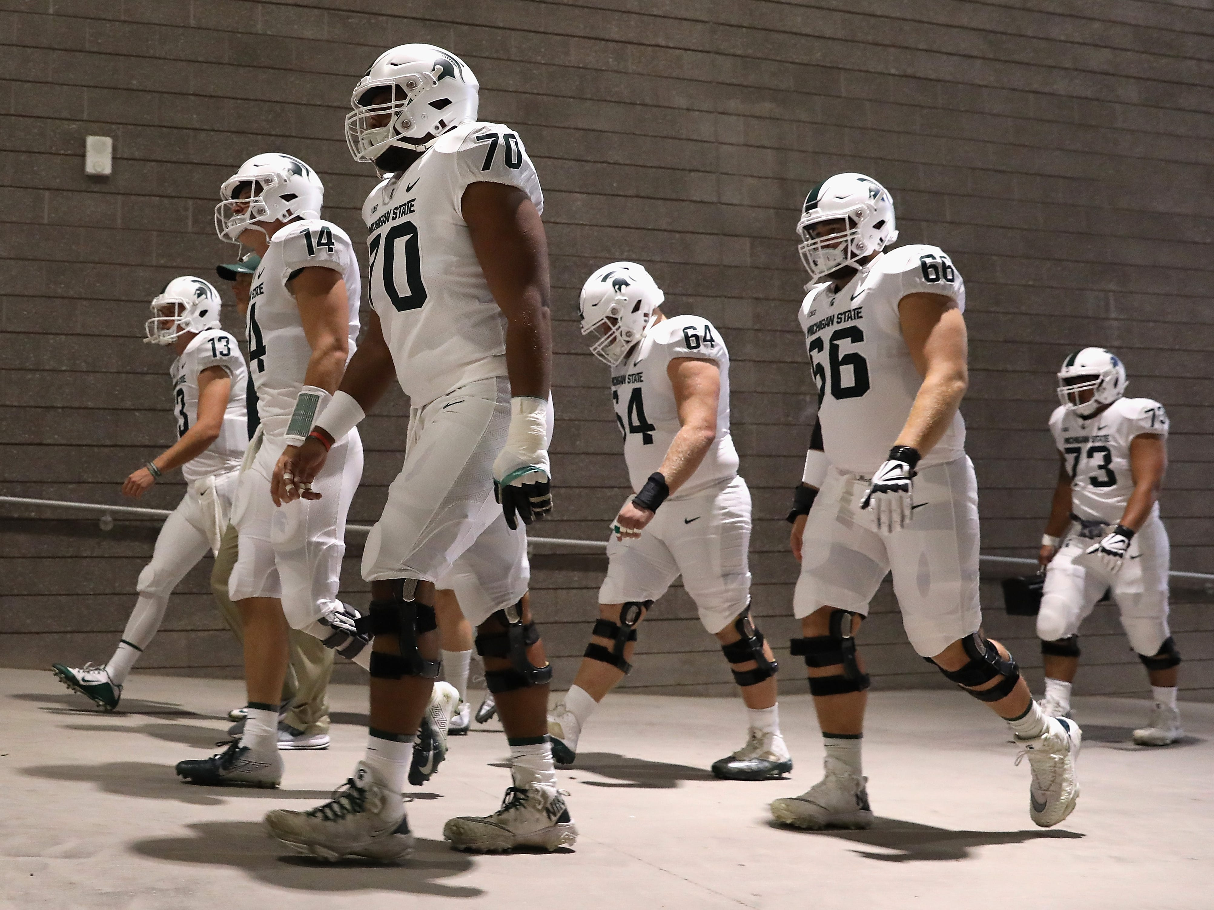 (L-R) Offensive lineman Jacob Isaia #73, quarterback Brian Lewerke #14 and offensive lineman Tyler Higby #70 of the Michigan State Spartans lead teammates out of the tunnell before the college football game against the Arizona State Sun Devils at Sun Devil Stadium on September 8, 2018 in Tempe, Arizona.
