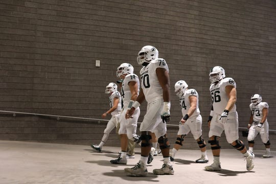 Michigan State quarterback Brian Lewerke (14) walks up the tunnel at Sun Devil Stadium on Saturday with centers Tyler Higby (70),  Matt Allen (64), Jacob Isaia (73) and center/guard Blake Bueter (66).