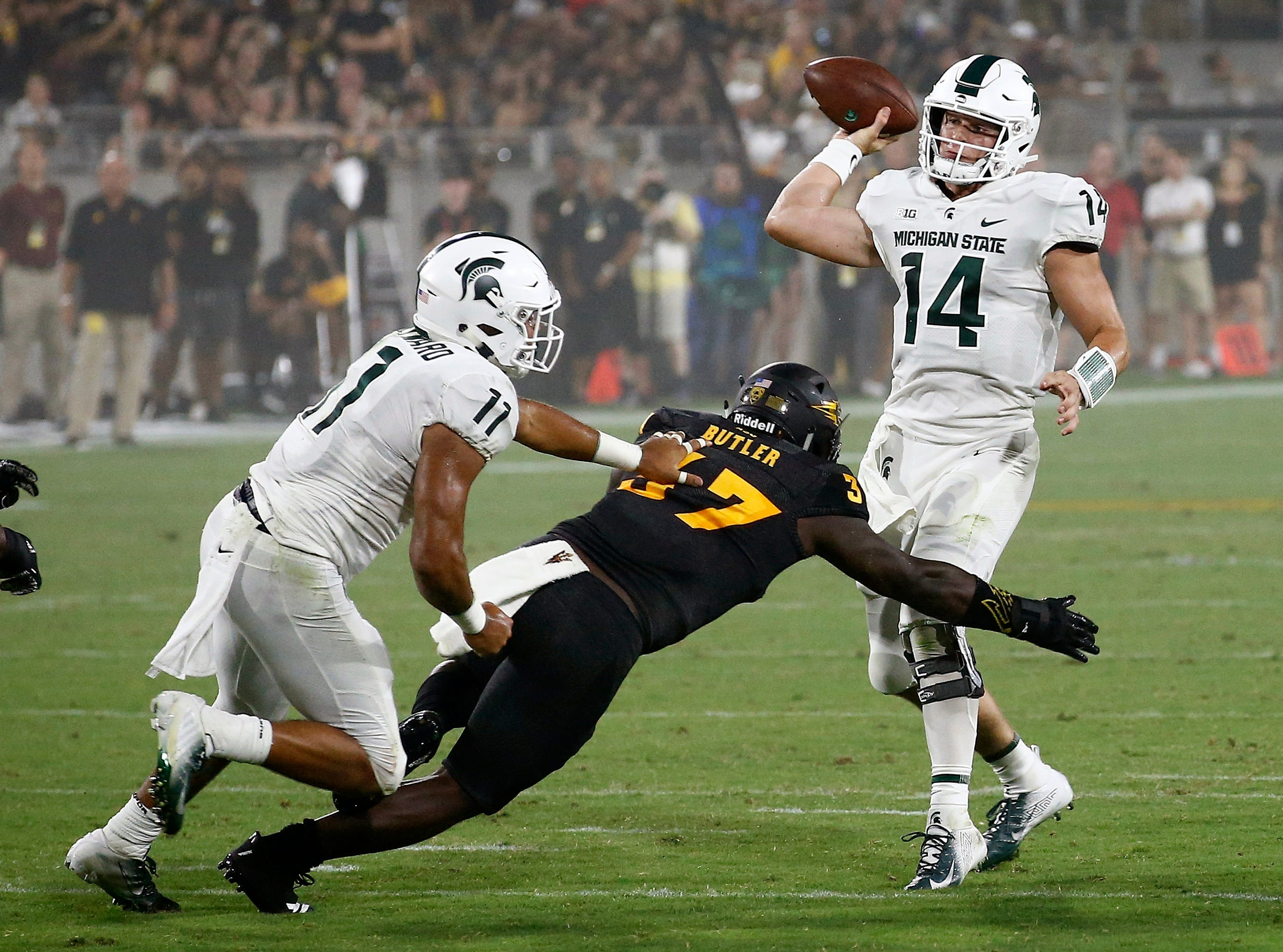 Michigan State quarterback Brian Lewerke (14) gets off a pass as he is pressured by Arizona State linebacker Darien Butler (37) as Michigan State running back Connor Heyward (11) tries to make a block during the first half of an NCAA college football game Saturday, Sept. 8, 2018, in Tempe, Ariz. (AP Photo/Ross D. Franklin)