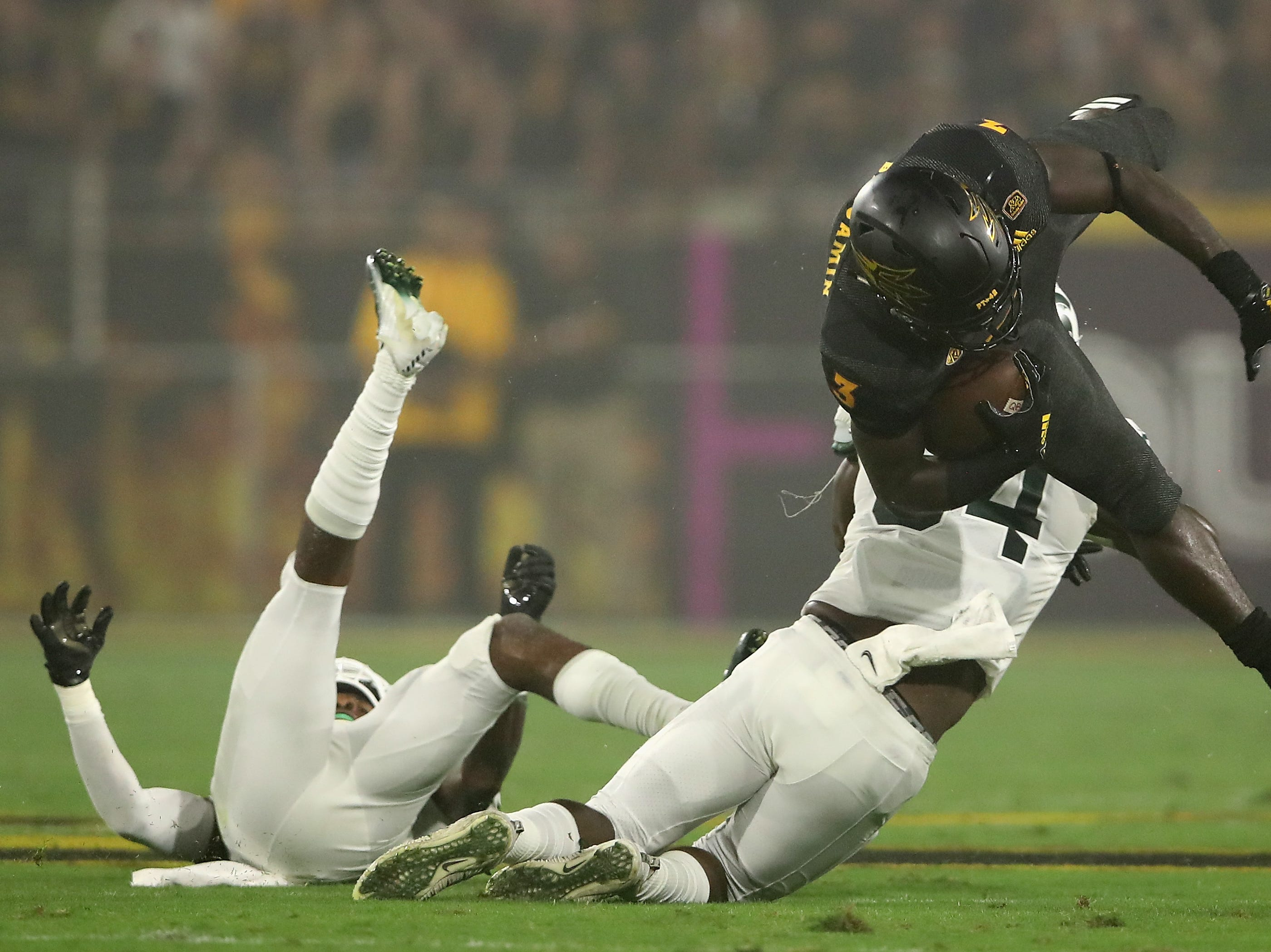 Running back Eno Benjamin #3 of the Arizona State Sun Devils is tackled by linebacker Antjuan Simmons #34 of the Michigan State Spartans during the first half of the college football game at Sun Devil Stadium on September 8, 2018 in Tempe, Arizona.