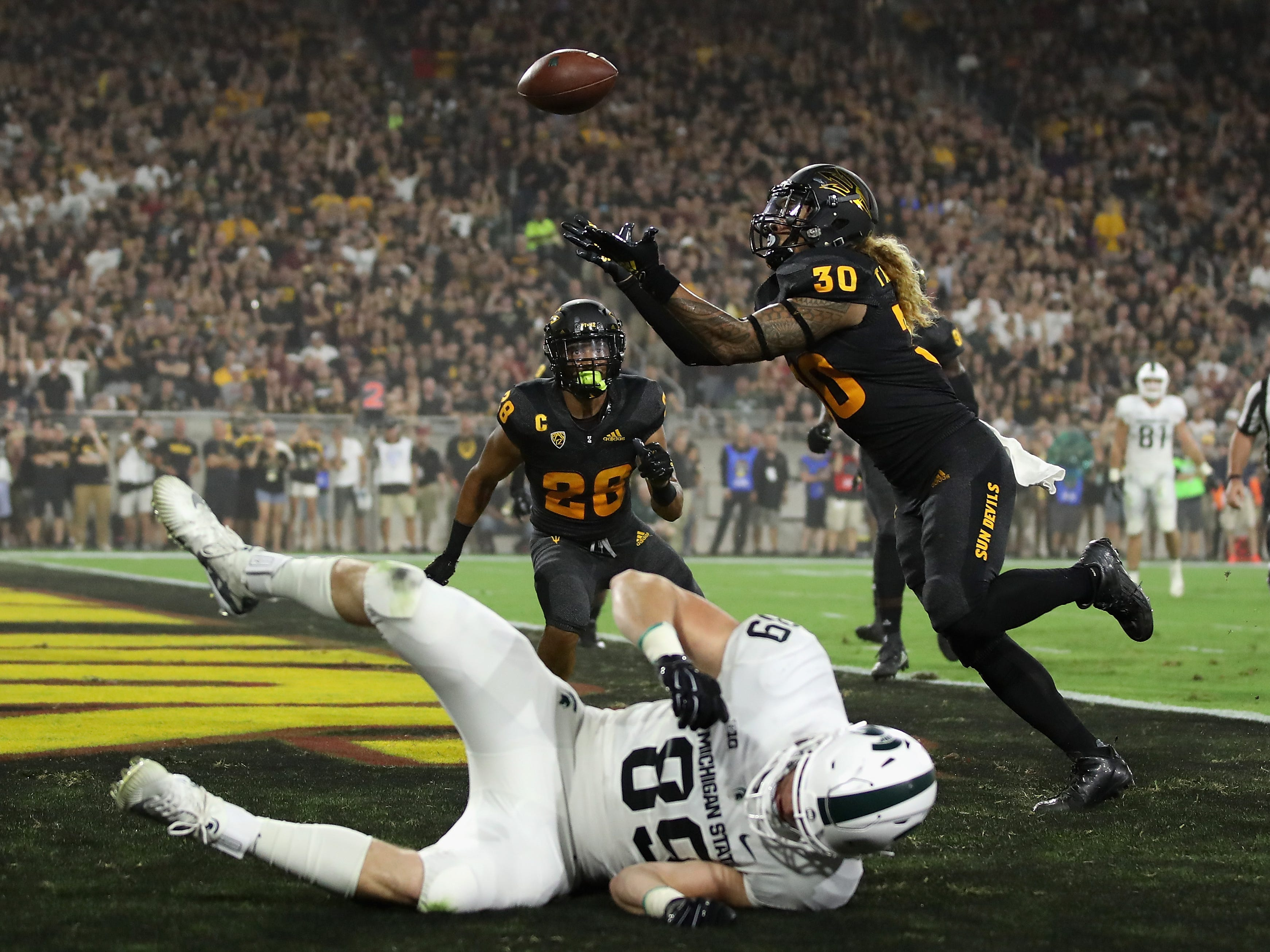 Defensive back Dasmond Tautalatasi #30 of the Arizona State Sun Devils intercepts a pass intended for tight end Matt Dotson #89 of the Michigan State Spartans during the first half of the college football game at Sun Devil Stadium on September 8, 2018 in Tempe, Arizona.