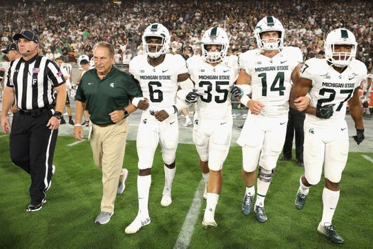 (R-L) Khari Willis #27, Brian Lewerke #14, Joe Bachie #35, David Dowell #6 and basketball head coach Tom Izzo of the Michigan State Spartans walk out to midfield for the coin toss to the college football game against the Arizona State Sun Devils at Sun Devil Stadium on September 8, 2018 in Tempe, Arizona.