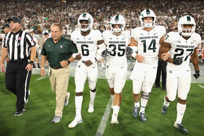 MSU basketball coach Tom Izzo, here arm in arm with MSU's football captains before a game at Arizona State in 2018, is devastated by the loss of football season.