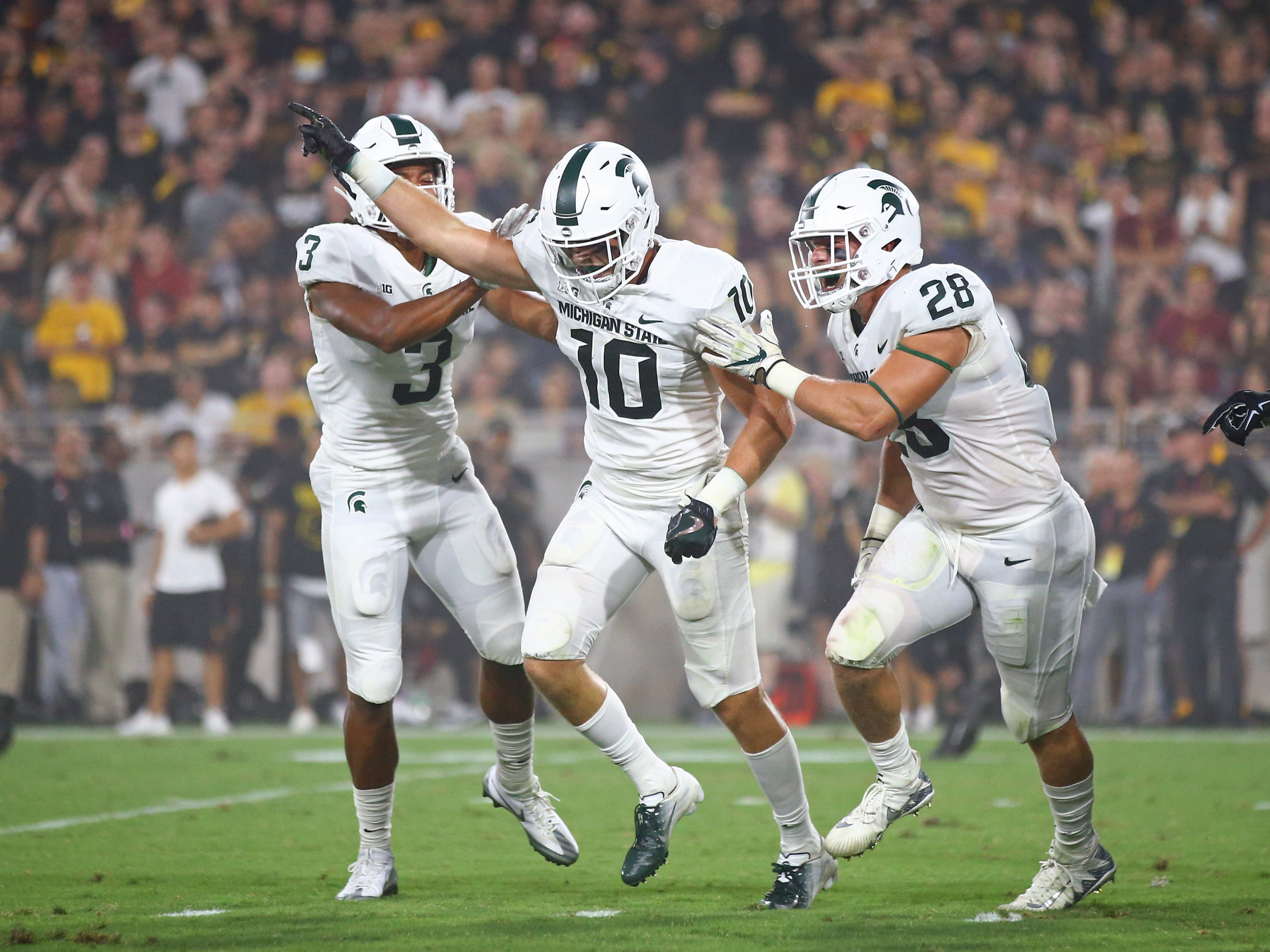 Michigan State Spartans safety Matt Morrissey (10) celebrates a second quarter interception with safety Xavier Henderson (3) and linebacker Jon Reschke (28) against the Arizona State Sun Devils at Sun Devil Stadium. Mandatory Credit: Mark J. Rebilas-USA TODAY Sports