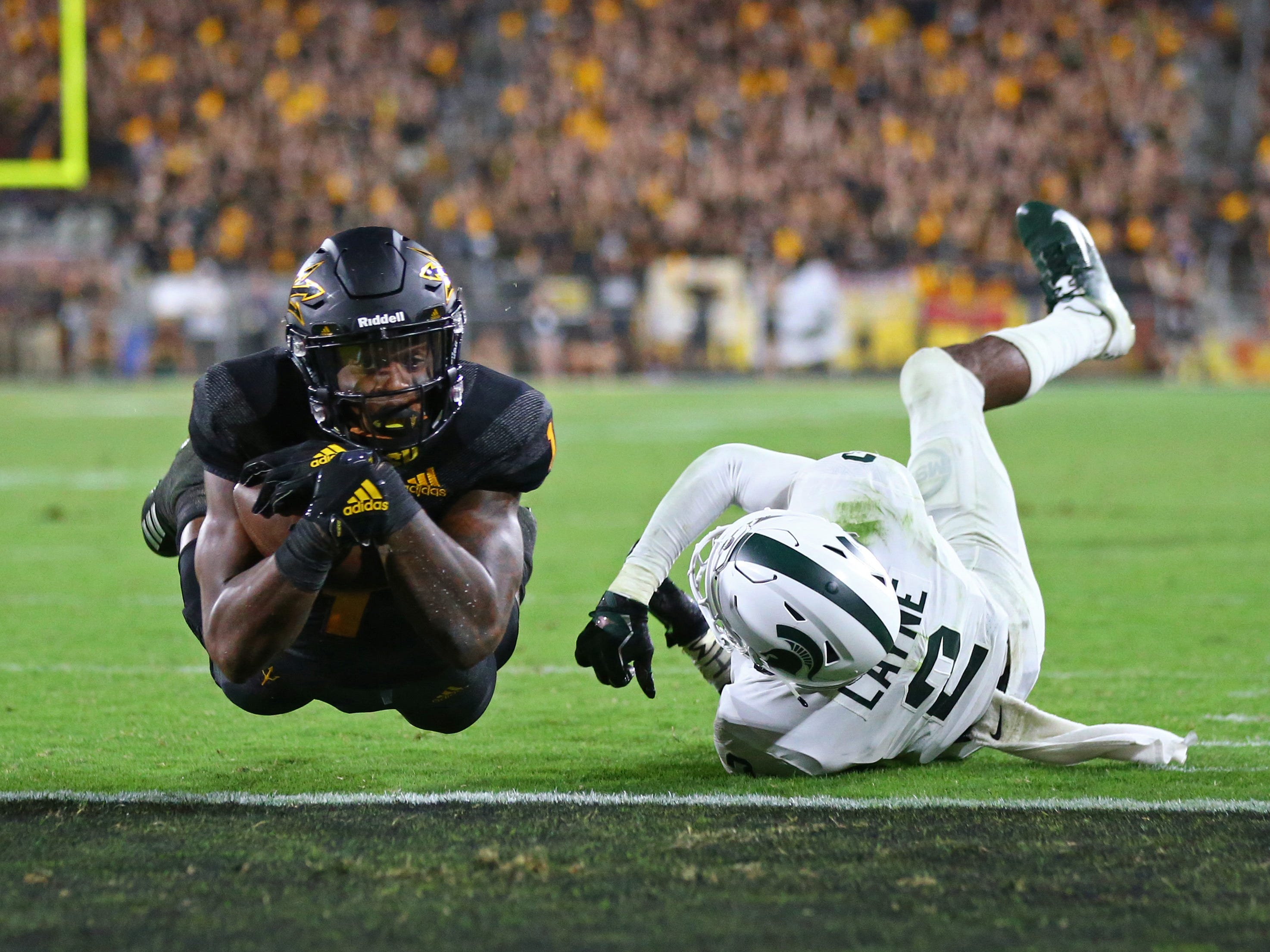Arizona State Sun Devils wide receiver N'Keal Harry (1) dives into the end zone for a touchdown against Michigan State Spartans cornerback Justin Layne (2) in the fourth quarter at Sun Devil Stadium.