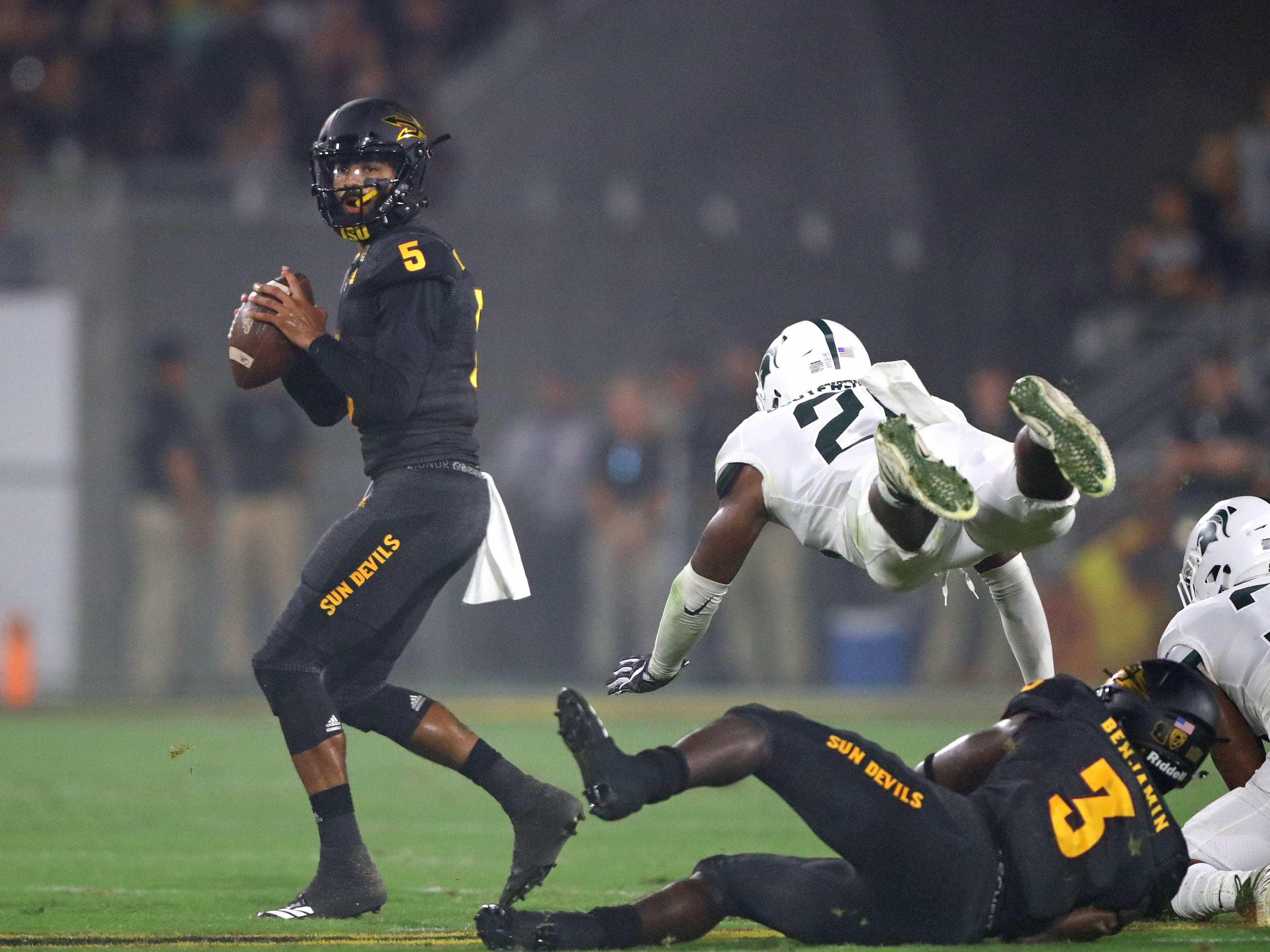 Arizona State Sun Devils quarterback Manny Wilkins (5) drops back to pass as Michigan State Spartans linebacker Brandon Bouyer-Randle (26) is upended as he attempts to tackle in the first half at Sun Devil Stadium.