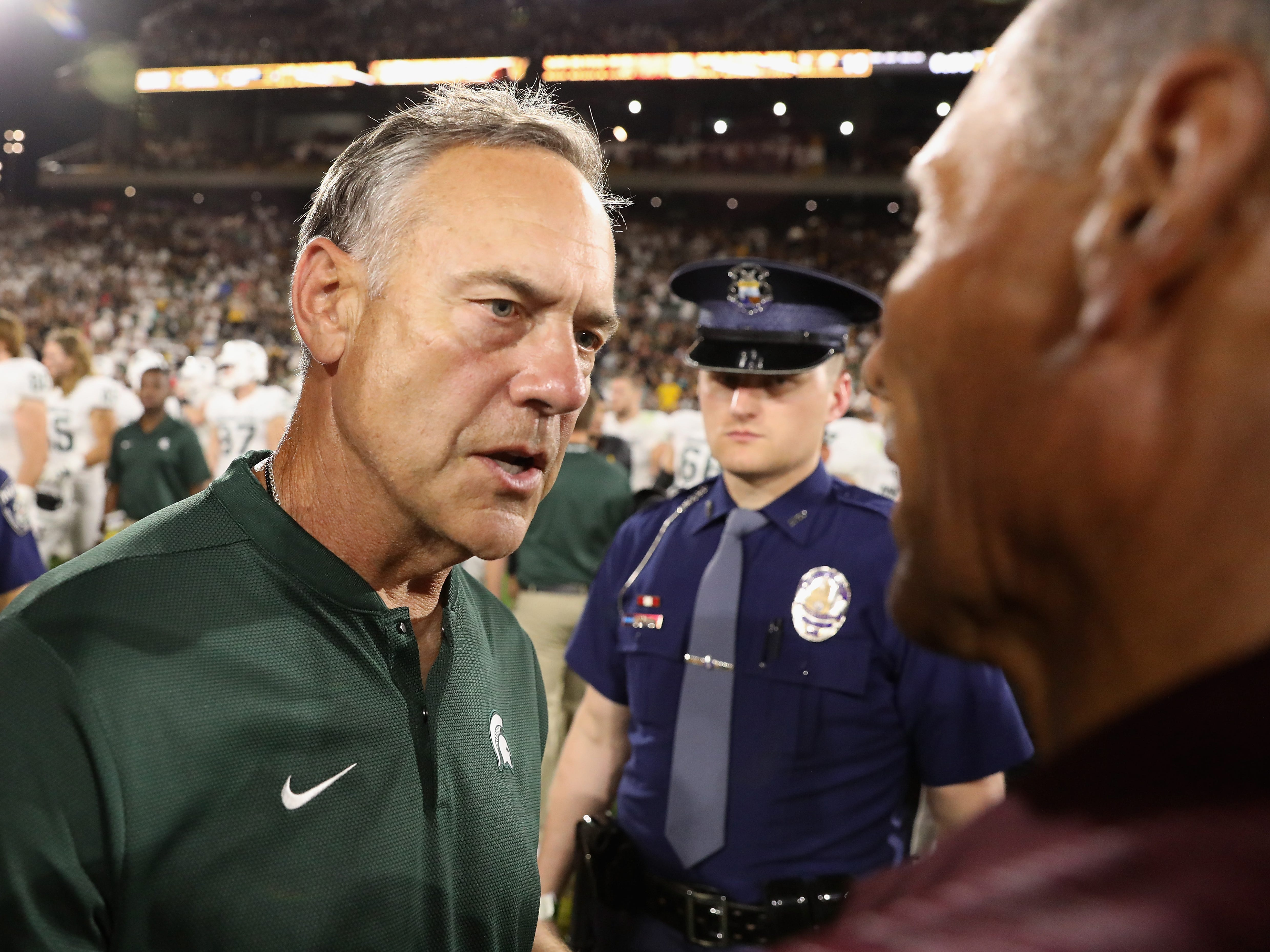 Head coach Mark Dantonio (L) of the Michigan State Spartans greets head coach Herm Edwards of the Arizona State Sun Devils following the college football game at Sun Devil Stadium on September 8, 2018 in Tempe, Arizona.  The Sun Devils defeated the Spartans 16-13.