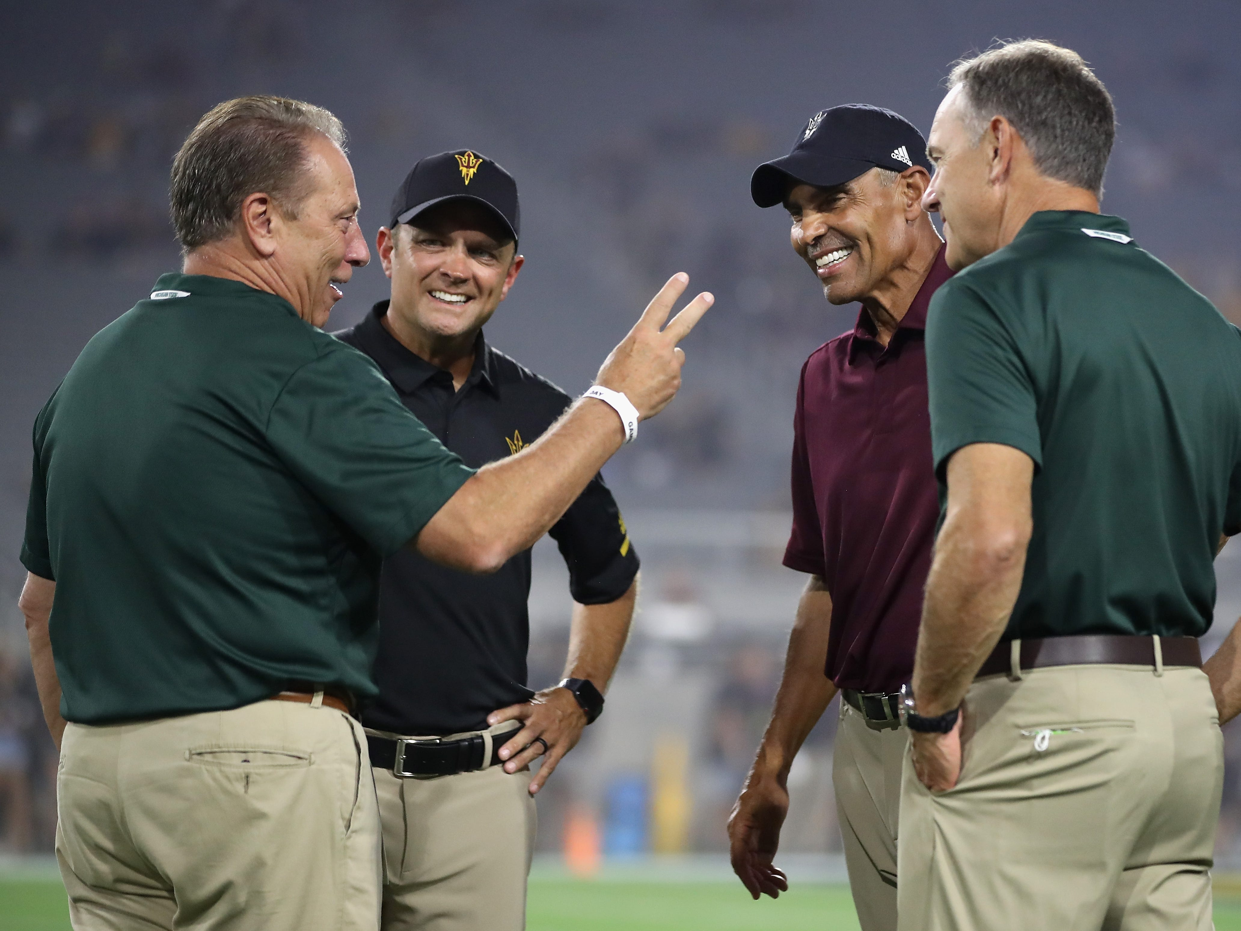 Head coach Herm Edwards (second from right) and defensive coordinator Danny Gonzales (second from left) of the Arizona State Sun Devils talk with college basketball coach Mike Izzo (L) and head coach Mark Dantonio (R) of the Michigan State Spartans before the college football game at Sun Devil Stadium on September 8, 2018 in Tempe, Arizona.