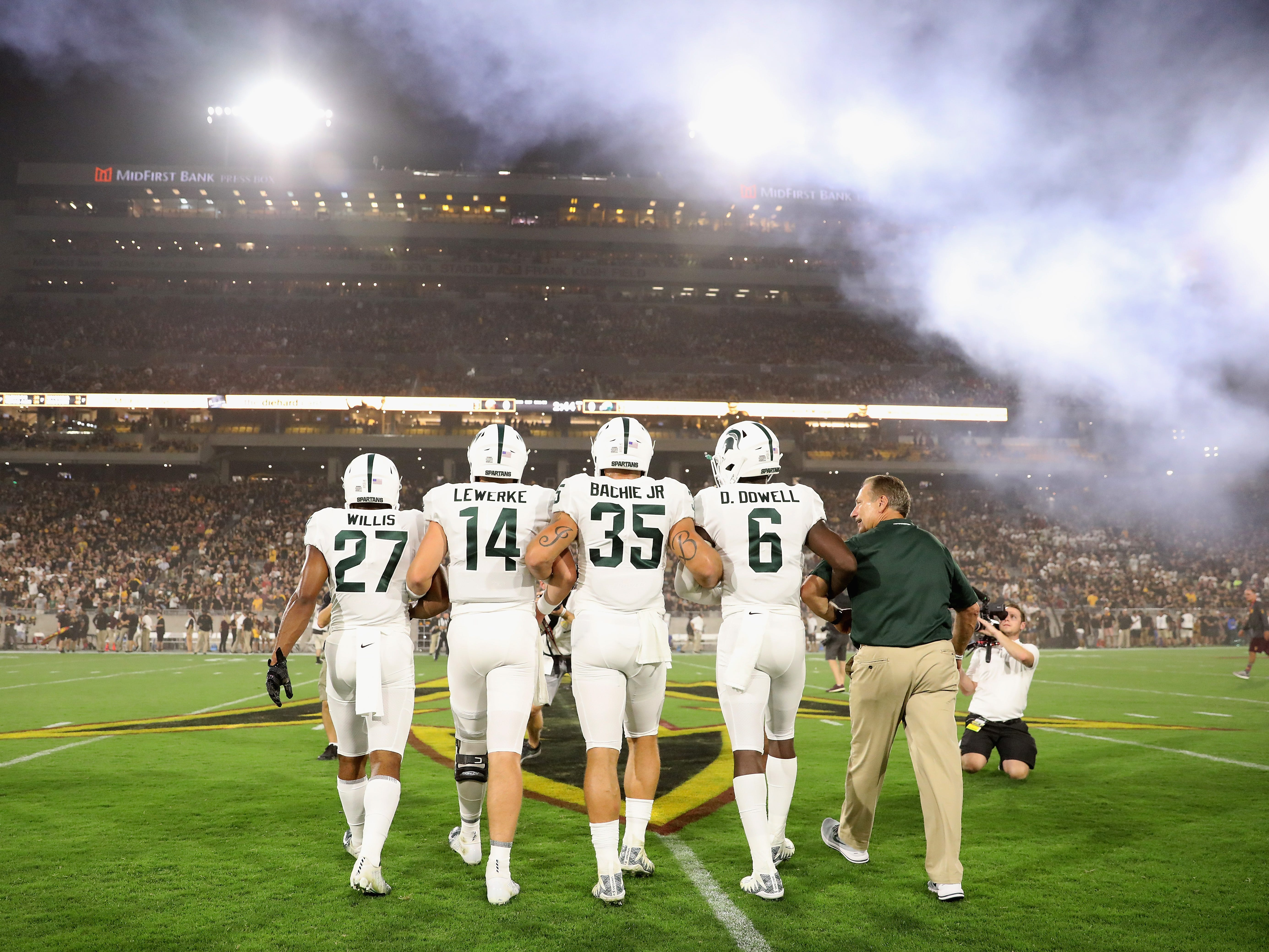 (L-R) Khari Willis #27, Brian Lewerke #14, Joe Bachie #35, David Dowell #6 and basketball head coach Mike Izzo of the Michigan State Spartans walk out to mid field for the coin toss to the college football game against the Arizona State Sun Devils at Sun Devil Stadium on September 8, 2018 in Tempe, Arizona.
