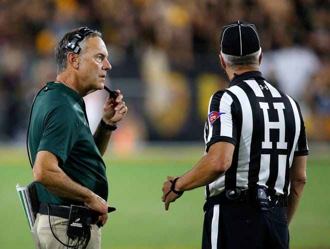 Michigan State head coach Mark Dantonio, left, calls a timeout as he talks with an official during the second half of an NCAA college football game against Arizona State Saturday, Sept. 8, 2018, in Tempe, Ariz. Arizona State defeated Michigan State 16-13.