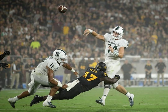 Quarterback Brian Lewerke #14 of the Michigan State Spartans throws a pass under pressure from linebacker Darien Butler #37 of the Arizona State Sun Devils during the first half of the college football game against the Arizona State Sun Devils at Sun Devil Stadium on September 8, 2018 in Tempe, Arizona.